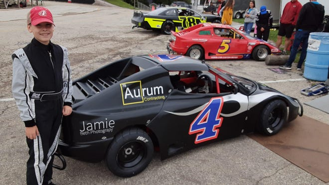 Rockford racer Carter Nilson, 10, stands next to the mini-race car that he rode to his first Bandolero main event victory on Sunday.