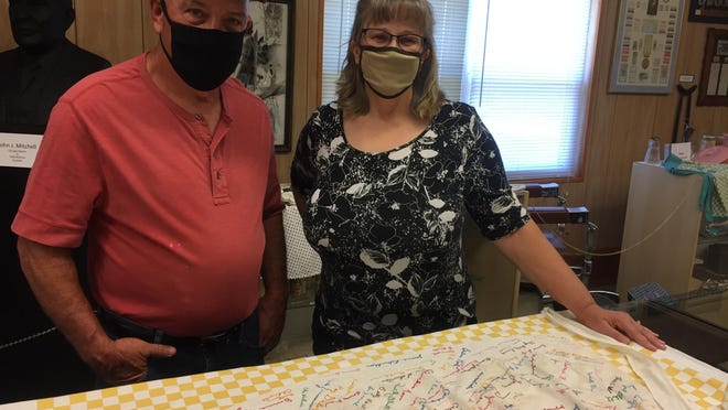 (Left to right) Greg and Pat Sinn, both of Tremont, examine a vintage kitchen apron embellished with signatures and messages from past area residents.