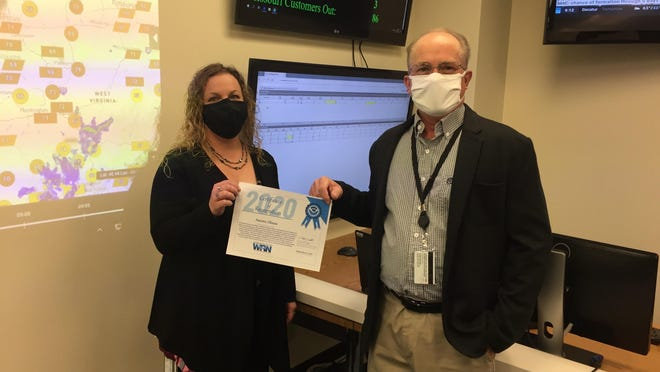 """Heather Lowrey, emergency response specialist, and Larry Magelitz, manager, Crisis Management, display the """"Ambassador or Excellence"""" award that Ameren Illinois received from the National Weather Service."""