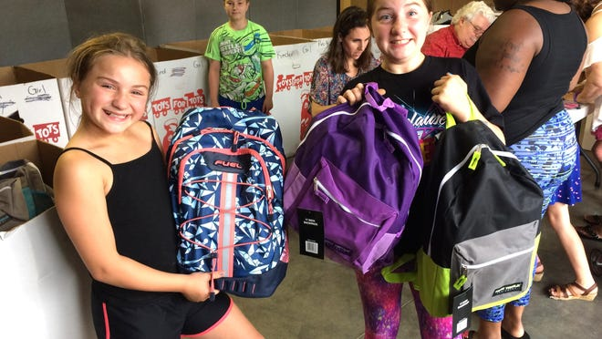 """Students excitedly pick up their backpacks of school supplies from a previous Greater Ottawa County United Way Stuff The Bus"""" drive. This year's drive is underway and ends Monday, Aug. 3."""