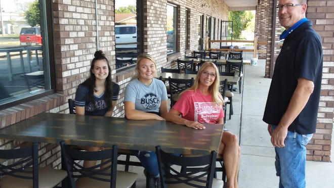 Hartley Suchy, director of operations and general manager for 32 Taps Tavern in Carleton, meets with some of his employees in the outdoor dining area that hopes to attract more customers to the restaurant. Seated are (from left) Anna Glasgow, Bailey Barnhart and Tricia Hammill.