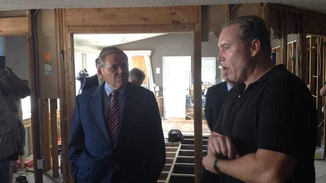 Doug Quinn (right) shows U.S. Sen. Robert Menendez, D-N.J., around his Sandy-ruined Toms River home . Quinn still is   in a struggle   over the payout for his flood insurance policy.
