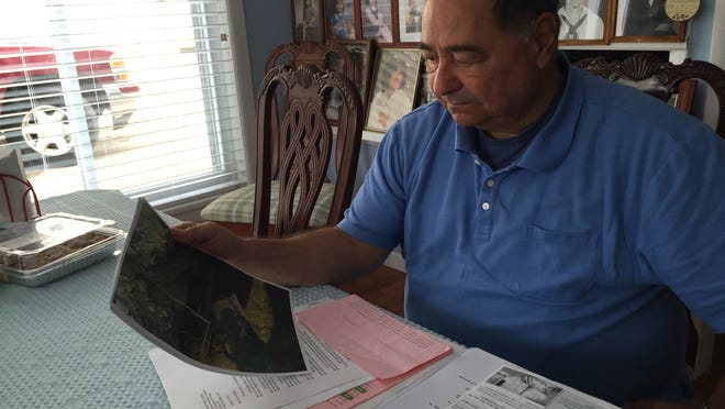 Stephen Tassie looks over paperwork in his Point Pleasant home. Press on Your Side helped him get a $6,700 reimbursement after a contractor built a gas line through his sewer pipe.