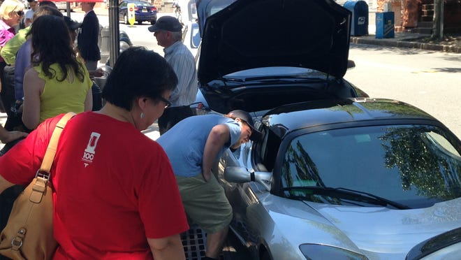 People check out a group of Tesla Motors electric cars lining West State Street outside the New Jersey Statehouse in June 2014.