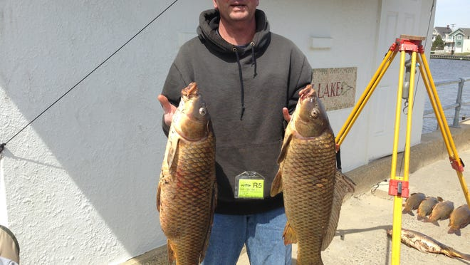 Dave DeGraw, Shark River Hill, with the 13.13-pound carp (left) that took the top prize in the Deal Lake Carp Fishing Contest.