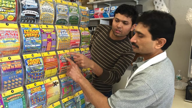 Bipin Patel (right), owner of Pinebrook Deli in Tinton Falls, points to a scratch-off ticket of the kind a New Brunswick man purchased at the store April 11. The ticket was worth $2,500 a week for life.