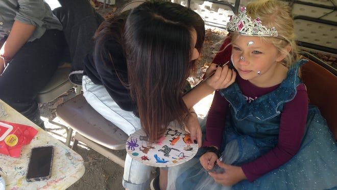 Six-year-old Eleanor Kruser, of Binghamton, in costume as the sticker princess, gets her face painted by Binghamton University student Jessica Huang, 20, of Long Island, during Howloween at the Zoo on Sunday.