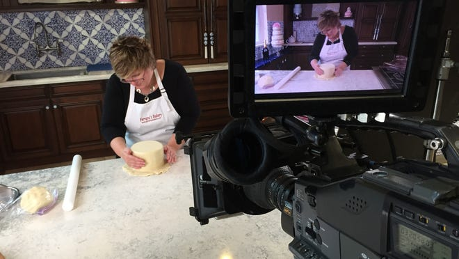 """Chef Angela Ferrara-McEllin covers a wedding cake in fondant icing while taping an episode of the Discovery Channel's series """"How It's Made"""" at the Vintage Living Marketplace in Rockledge on Monday."""