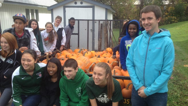 Some of the 30 volunteers from Winooski High School take a break after loading a portion of the 700-plus hand-carved pumpkins on a trailer Saturday during national Make A Difference Day.