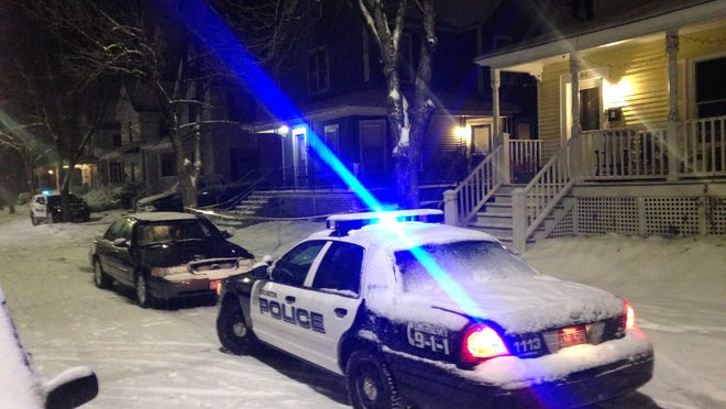 Burlington police cars parked in front of a home on Greene Street on Saturday where a 23-year-old man was found dead.