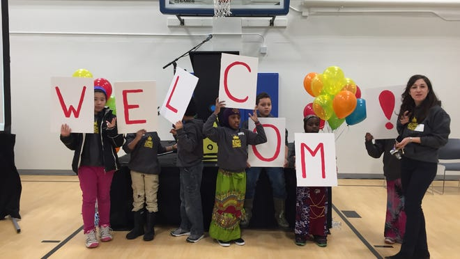 Children from the King Street Center Wednesday hold up signs at the grand opening.
