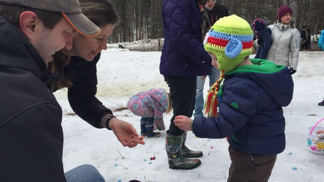 """Jacoby Stander, 2, of Montpelier gets some help from his parents, Jen and Thad Stander. Jacoby spent some time munching on his chocolate treats instead of filling up his Easter basket. """"I figured this is how it would go — eating and standing,"""" said Jen Stander."""
