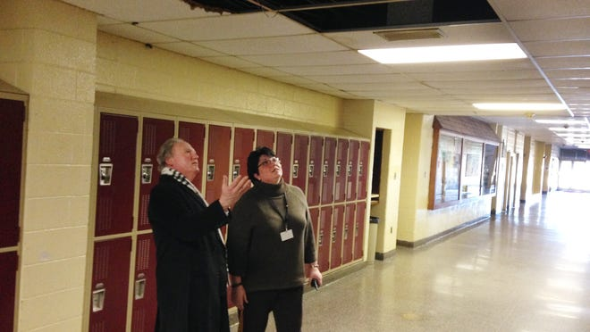 Glassboro School District Superintendent Mark J. Silverstein and high school Principal Danielle Sneathen look at a ceiling hole Friday. A $1.3 million roof project is among several infrastructure repairs up for a vote in a March 10 referendum.