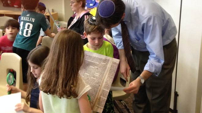 Rabbi Micah Peltz works with students in understanding letters in the Holocaust Torah.