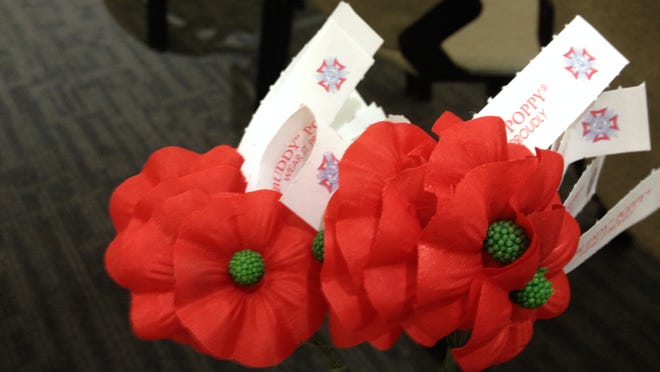 """The Buddy Poppy is a red paper flower with a tag to """"Wear it Proudly."""""""