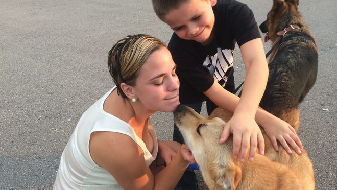 Candace Mora and her son, Evan Mora, 9, lavish foster dog Maxine with love during a break in a training session. Maxine will be going to her new forever home this week.