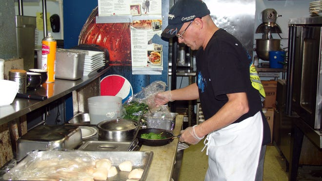 Line cook Gary McCoy prepares jumbo scallops at Oscar Rose Steak and Seafood House in Coshocton.