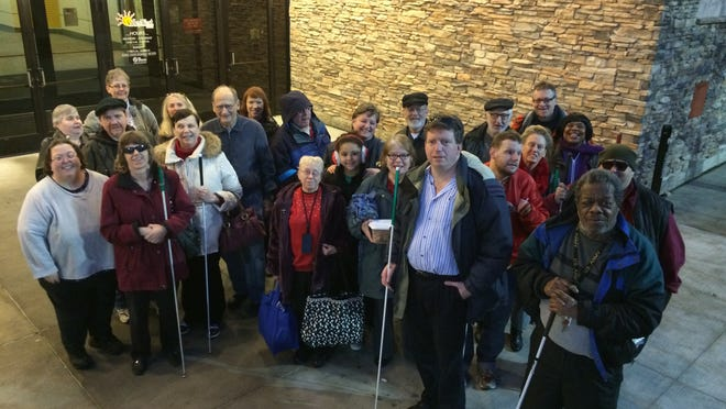 About two dozen visually impaired people and their sighted companions gathered at Valley West Mall to board a party bus bound for Water Works Park, where interpreters will described the Jolly Holiday Lights.