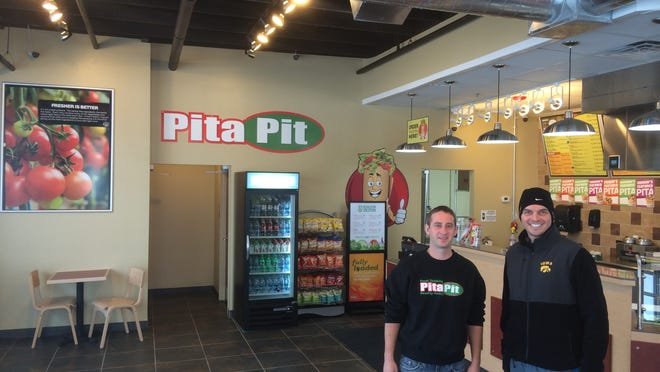 Mike Rink, left, welcomed Matt Lowe, the first customer to the new Pita Pit restaurant in Urbandale. The eatery opened Jan. 6 at the northwest corner of Merle Hay Road and Aurora Avenue.