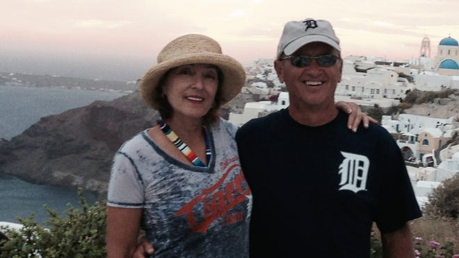 Tina Meier and Jim Meier, who is wearing the Old English D, in front of the cliffs in Oia, Greece, in September.