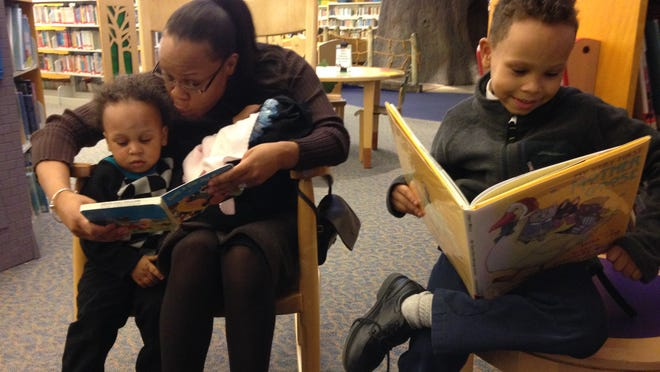 Dalayna Stepp, with 6-week-old Savannah hidden in a carrier on her lap, reads to 18-month-old Simon at the Southfield Public Library while Solomon, 7, dives into a book of his own.