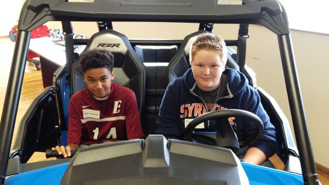 Ernie Davis Academy students who toured Hilliard Corp. in Elmira on Friday, National Manufacturing Day, clamored to take a seat in the side-by-side Polaris ATV displayed inside the company. Pictured are ninth-graders Jalen Townsend, left, and Alan Harvey.