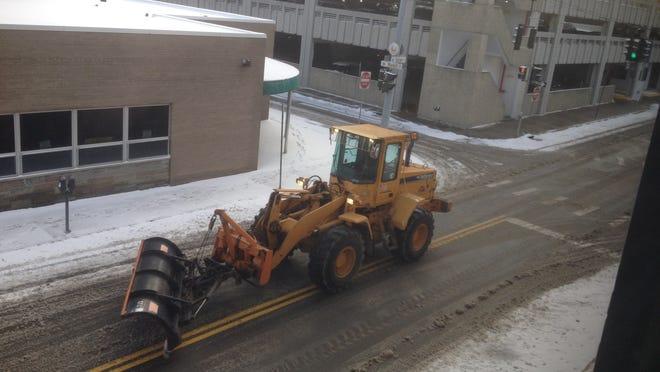 A City of Elmira worker clears snow from Baldwin Street near Market Street around 9:15 a.m. Thursday.
