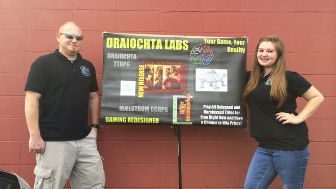 Jay Smith, chief executive officer, from left, and Taylor Musch, public relations and event coordinator, both for Draiochta Labs in Fond du Lac pose with the banner they display during gaming conventions.