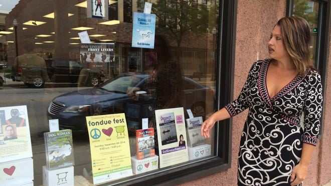Store Manager Stacey Morris talks about some of the authors who will visit Book World, 85 S. Main St., during Fondue Fest on Sept. 6.
