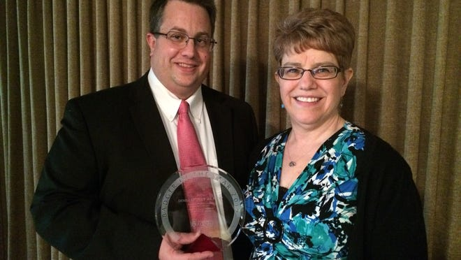 Denise Retzleff, right, accepts the Wisconsin Alumni Association Badger of the Year Award from Fond du Lac Chapter President Steve Leaman at the 2015 Founder's Day event.