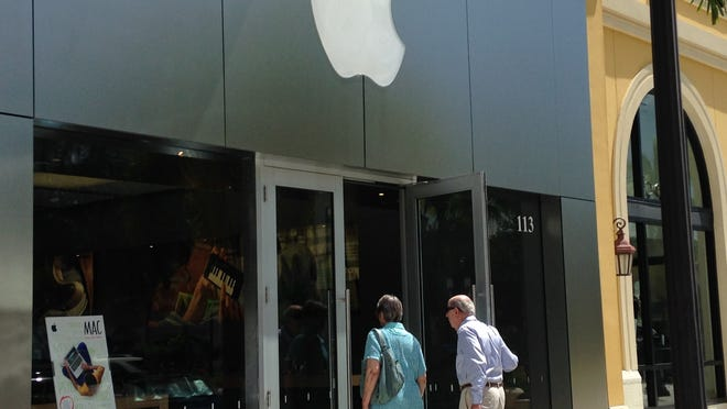 Customers enter the Apple Store on Tuesday at the Coconut Point Mall in Estero.