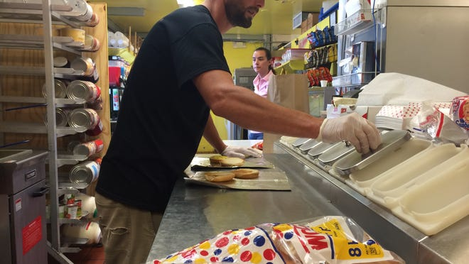 Nick Caruso prepares a burger as his wife, Rachel, waits to deliver it to a customer at Caruso's Eats and Treats in south Fort Myers.