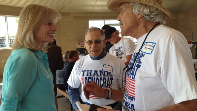 Mary Burke, running as a Democratic candidate for governor of Wisconsin, talks with Door County Democratic Party Chairman Garrett Cohn and Vice Chairman Bill Perloff (middle) at a picnic and rally Thursday evening at Sawyer Park in Sturgeon Bay.