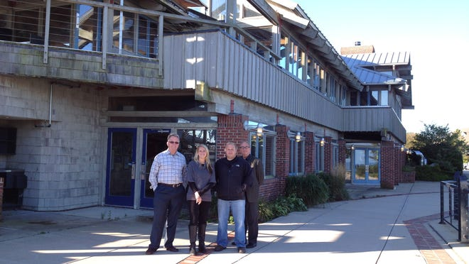 The former Applebee's restaurant will house two new businesses after remodeling, with DC Donut and Coffee Company on the lower level and Sonny's Pizzeria and Italian Bistro on top. From left, Bob Wolter, Laura and Jason Estes and Michael Schwantes stand outside the large deck.