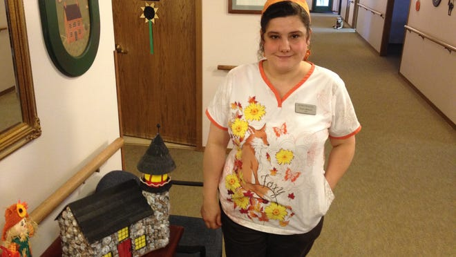 Triest Wright, CNA, with one of the homemade lighthouses created with residents of Bay Road Place in Algoma.
