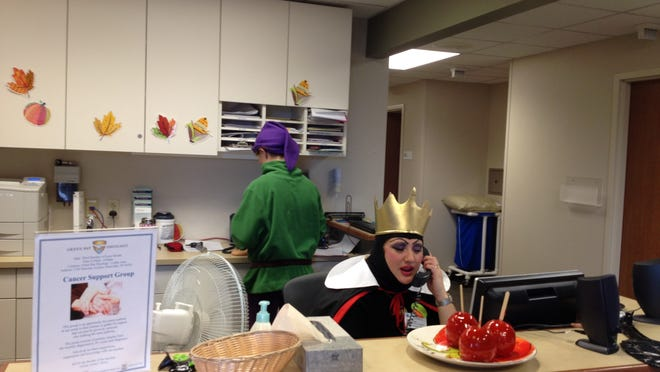 "Evil queen Amy Ellefson fields a call at the Door County Cancer Center on Thursday while Jessica Kaye (""Dopey"") works behind her."