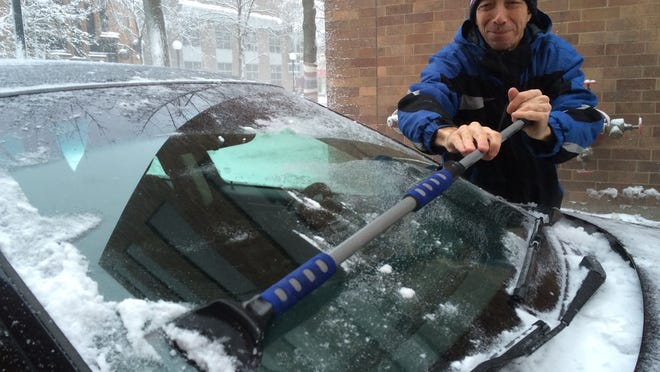 Ron Wright, 56, who works as a deliverer for the web-based Order Up app, scrapes snow from his windshield during Sunday's snowstorm.