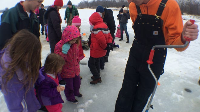 Will Downey, right, a volunteer for Take a Kid Outdoors, shows off a hole he drilled in frozen Sand Lake to kids at Iowa City's first Freeze Fest on Saturday afternoon.