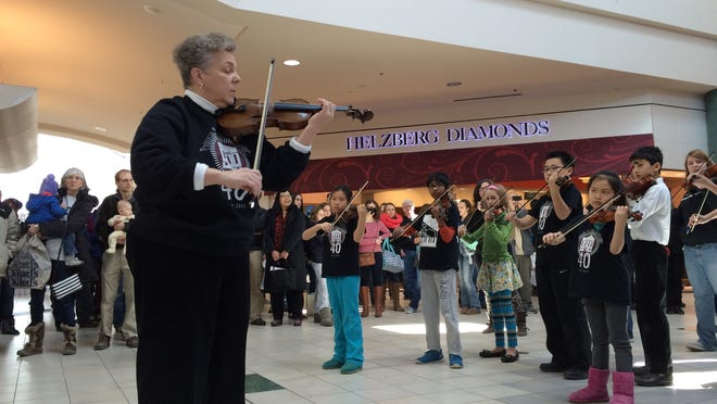 "Young students of the Preucil School of Music in Iowa City join Sonja Zeithamel, left, director of the school, as a group of about 100 of the school's students and teachers play Pachelbel's ""Canon"" during a flash mob at the Coral Ridge Mall on Sunday."