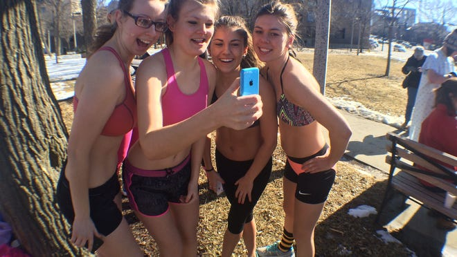 From left to right: Jill White, a UI sophomore, Aubrey Taylor, a senior, Becca Hott, a senior, and Anna Bruns, a senior, gather to take a selfie before the Nearly Naked Mile in downtown Iowa City Saturday morning.