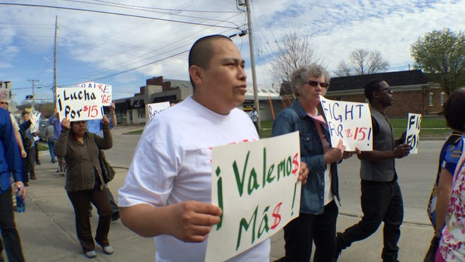 Marcial Hurtado marches with a group of about 80 demonstrators during Fight for $15 on Wednesday. Demonstrators marched to Sedona Staffing, a temporary staffing agency, to deliver a letter demanding more stable employment.