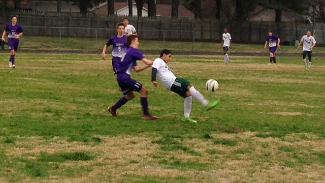 A JCM player looks to secure possession with a Trinity defender behind him Friday night.