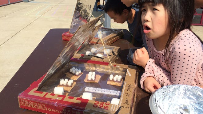 Kayla Xu checks out her s'more baking in a solar oven Wednesday at Cumberland Elementary School.