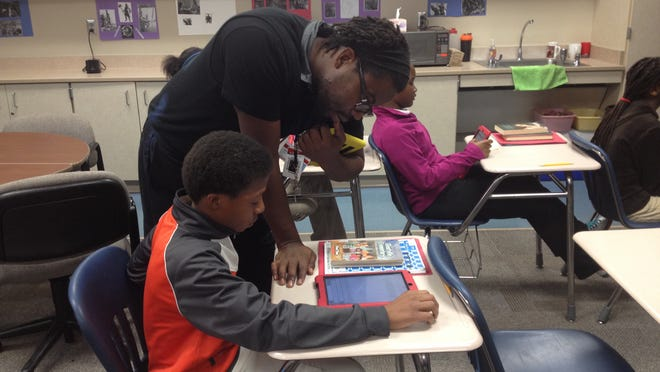 David Barrett teaches his sixth grade class about paragraph structure Wednesday at Lafayette Sunnyside Intermediate School. Community members and leaders believe hiring more minority teachers will help curb the number of suspensions and expulsions among local black youth.