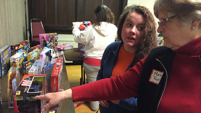 Parent Carley Garbison, left, and volunteer Marty Taylor pick out presents for Garbison's two sons at Central Presbyterian Church Saturday. The church was one of 24 sites participating in Lafayette Urban Ministry's Jubilee Christmas program, which gives free children's gifts to low-income parents.