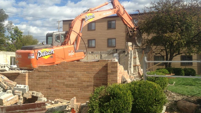 Crews demolish a law office Wednesday at the corner of Kedzie Street and Grand River Avenue in East Lansing. The office will be replaced by a new building with retail space on the first floor and apartments on the upper floors.