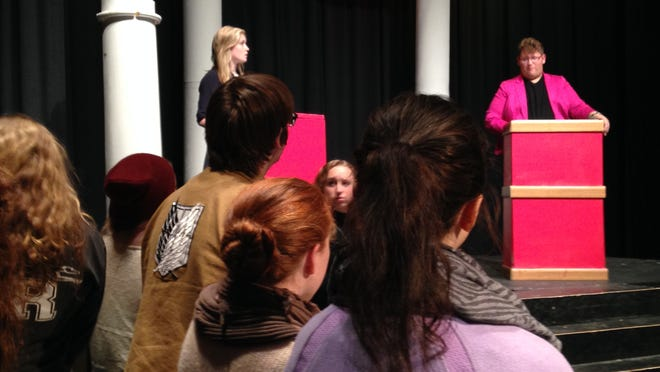 "Audience members in the cast of ""The Election"" listen as Dustin Larson as Mark Davenport and Samantha Ovresat as Christy Martin rehearse a debate scene."
