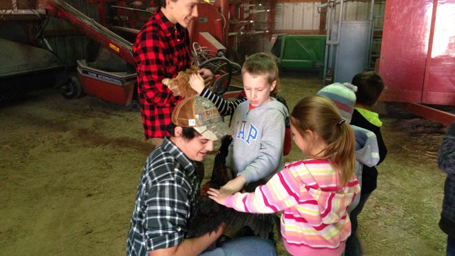 Kiel FFA President Jacob Bulitz (kneeling front) and Secretary Casey Klotz (standing back) teach Kiel Area School District kindergartners about chickens at the annual Day on the Farm event hosted at the farm of Roy and Bridget Seimen of Newton.