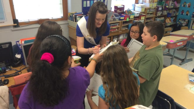 Wisconsin's 67th Alice in Dairyland, Zoey Brooks, autographs students' notebooks after giving a presentation on Wisconsin agriculture at Jefferson Elementary School in Manitowoc on Wednesday.