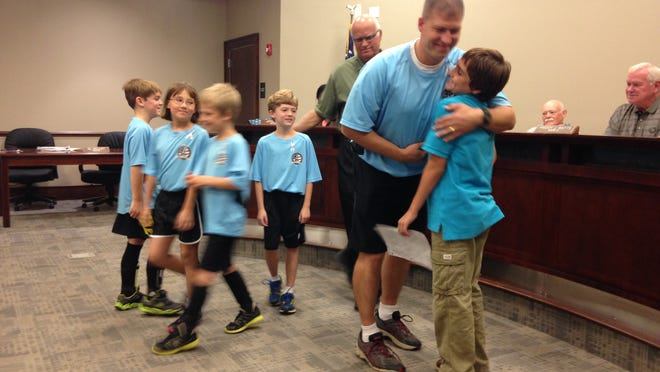 Shane Merillat, coach of Prattville's Sharks soccer team and also an Air Force master sergeant, embraces Rett Gabehart at the Millbrook City Council meeting last week. Rett, of Deatsville, shared his story of living and coping with type 1 diabetes in advance of November's National Diabetes Month and World Diabetes Day on Nov. 14.